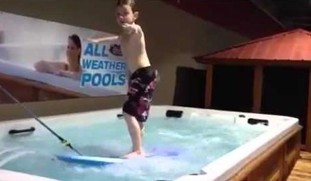Boy learning to surf in a All Weather Pool