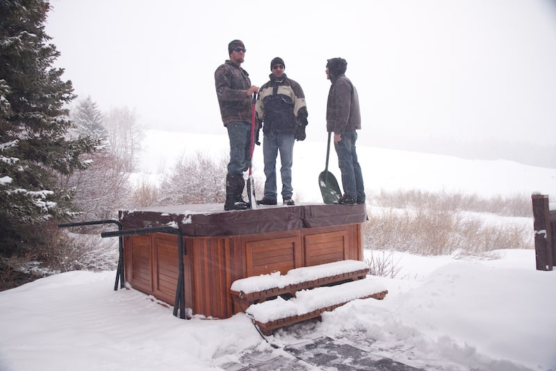 Men staying on the covered hot tub in the winter