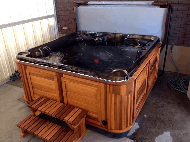 Arctic Spas Hot tub with red lights inside in the backyard
