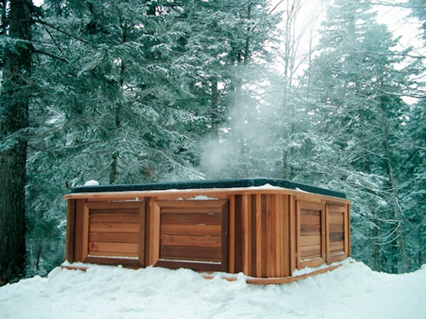 A hot tub in a snow forest